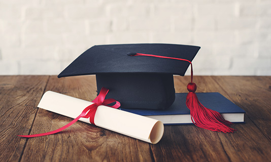 Graduate cap, scroll and textbook
